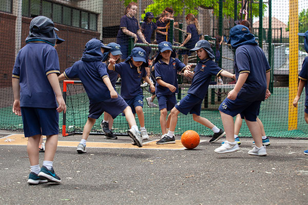 Students playing soccer out in school yard