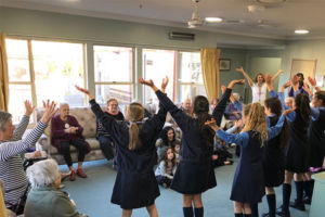 Students performing to an elderly audience