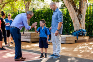 Principal high fiving a student with their parent