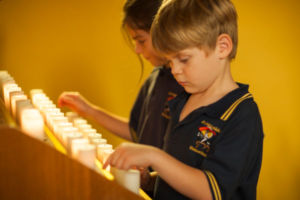 Student inside church turning on candle