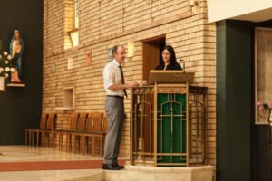 Two staff members reading at podium in church