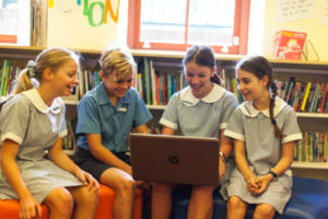 Four students collaborating around computers