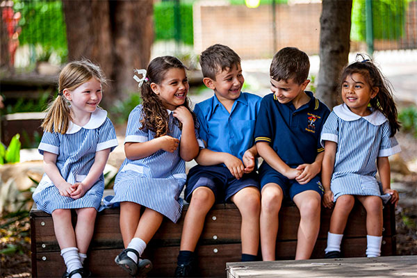 Students sitting on a bench smiling and chatting