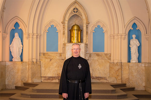 Father Gary Perritt standing and smiling inside church