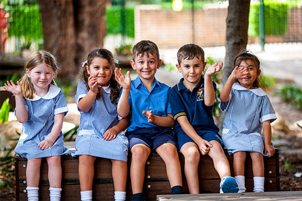 Students at St Joan of Arc Catholic Primary School smiling and waving